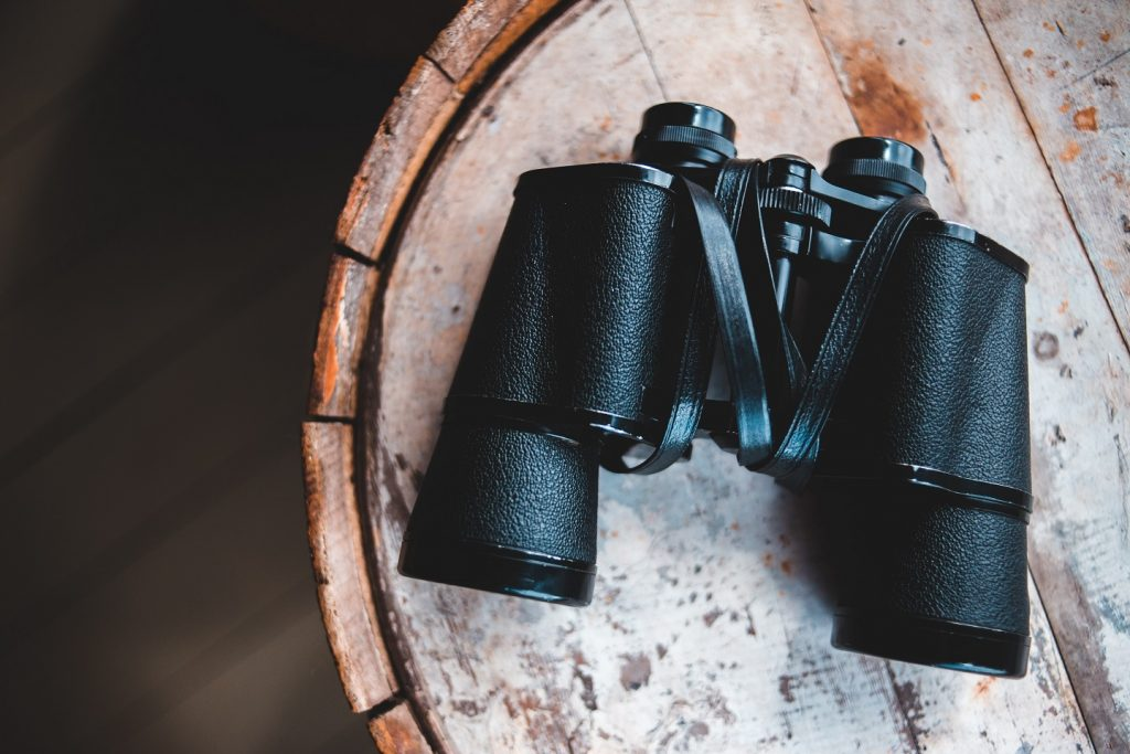 picture of  binoculars on wooden table