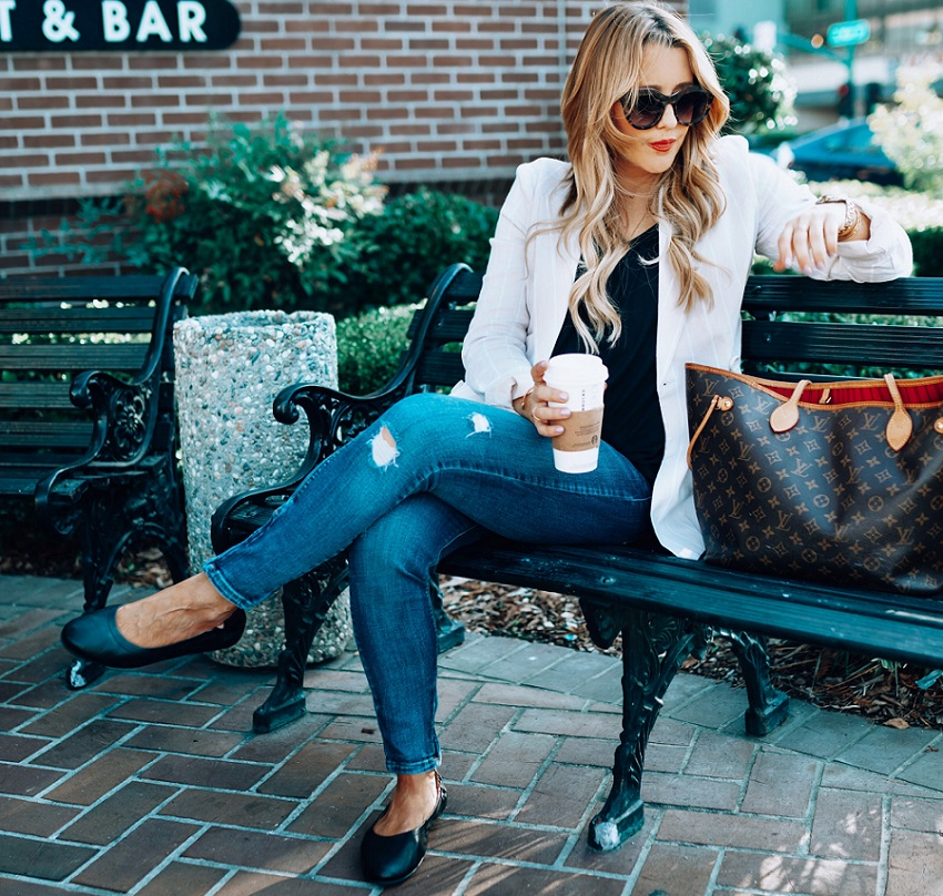 picture of a woman on a bench drinking coffee wearing stylish outfit and ballerina shoes
